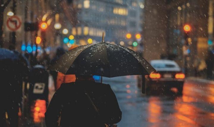 洪水・氾濫などの水害を前に傘をさす男性