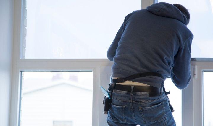 台風対策で窓ガラス飛散防止フィルムを貼る男性